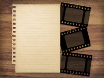 Paper and filmstrips. Yellowed paper and filmstrips on wood background Royalty Free Stock Photo