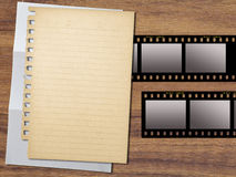 Paper and filmstrips. Yellowed paper and filmstrips on wood background Stock Image