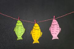 Paper fish hanging on string near chalkboard. April fool`s day celebration royalty free stock photos