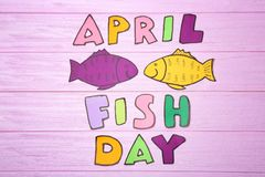 Paper fish and phrase. `April fish day` on color background stock image