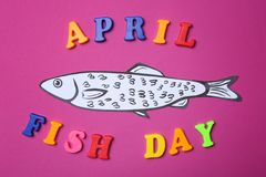 Paper fish and phrase. `April fish day` on color background royalty free stock photography