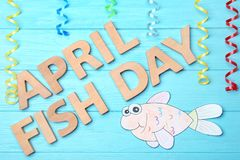 Paper fish and phrase. `April fish day` on color background Royalty Free Stock Photos