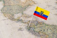 Ecuador flag pin on world map. Paper flag pin of Ecuador on a world map showing neighboring countries. Officially the Republic of Ecuador, it is a a Stock Photos