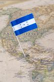 Honduras flag pin on a world map. Paper flag pin of Honduras on a world map showing neighboring countries. It is a republic in Central America. Concept image royalty free stock images