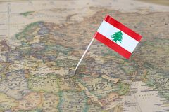 Lebanon map and flag pin. Paper flag pin of Lebanon on a world map showing neighboring countries. Officially known as the Lebanese Republic, it is an Arab stock images