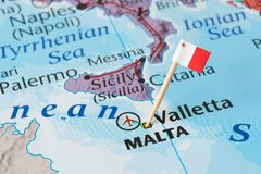Malta map and flag pin. Paper flag pin of Malta on a world map showing neighboring countries. It is a Southern European island country consisting of an stock photo