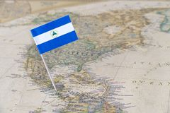 Nicaragua flag pin on world map. Paper flag pin of Nicaragua on a world map showing neighboring countries. Officially the Republic of Nicaragua, it is the stock photos