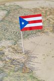 Puerto Rico flag pin on a world map Royalty Free Stock Image