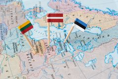 The Baltic states map with flag pins. Paper flag pins of three Baltic states - Lithuania, Latvia, Estonia on a world map royalty free stock image