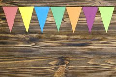 Paper  flags  party garland  on wooden background.  Stock Image