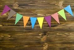 Paper  flags  party garland  on wooden background.  Royalty Free Stock Photo