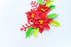 Paper flower poinsettia and leaves of holly royalty free stock photo