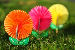 Paper flowers. On the grass in spring - focus to the first flower royalty free stock photography