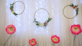Paper flowers decoration. Big corrugated paper flowers hoops rings on the white background and garland home stage design pink yellow green colors stock video footage