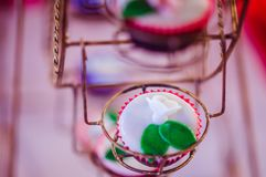 Pink cup cakes on wheels stock photography