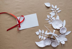 Paper flowers and gift. Small paper flowers and leaves  and  gift, white csrd Royalty Free Stock Photos