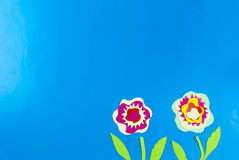 Paper flowers and seedlings. Paper flowers growing from seedlings on blue background Royalty Free Stock Photo