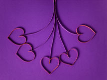 Paper flowers with hearts on purple background Royalty Free Stock Images
