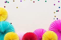 Paper flowers on light table top view. Festive or party background. Flat lay style. Copy space for text. Birthday greeting card. Paper flowers on light table stock photography