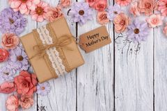 Paper flowers with Mother`s Day gift and tag against white wood Stock Image