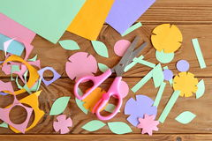Paper flowers, paper sheets, scissors, paper scrap on a wooden table Royalty Free Stock Photography