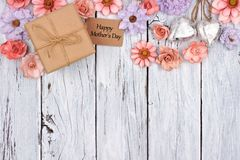 Paper flowers top border with Mother`s Day gift and tag over wood Stock Images