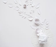 Paper flowers on the white background. Small paper flowers and leaves on the white background and white gift Royalty Free Stock Image