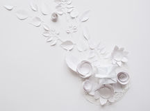 Paper flowers on the white background. Small paper flowers and leaves on the white background and white gift Royalty Free Stock Photos
