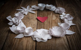 Paper flowers on the wood background. Paper flowers on wood background in the form of a circle and red heart Stock Images