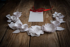 Paper flowers on the wood background. Paper flowers on wood background in the form of a semicircle and white card Royalty Free Stock Photos