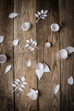 Paper flowers on the wood background. Small paper flowers and leaves on wooden background Stock Images