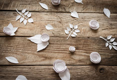 Paper flowers on the wood background. Small paper flowers and leaves on wooden background Stock Photo