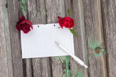 Paper and flowers. Flowers and paper on wooden background Stock Images