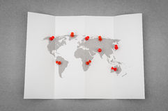 Paper folded world map  with red Pin Pointer . Royalty Free Stock Photos