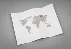 Paper folded world map  with red Pin Pointer . Royalty Free Stock Photography