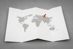 Paper folded world map  with red Pin Pointer . Stock Photos