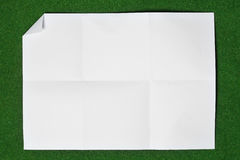 Paper folded and wrinkled on grass. Royalty Free Stock Image