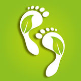 Paper foot prints with green leaves Stock Photos