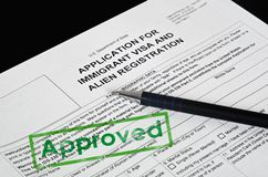 Paper Form US immigration visa lies on the black surface. On paper the form of immigration visas to visit the United States is stamped APPROVED, is a fountain royalty free stock photos
