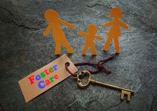 Paper foster care family. Of three with gold key Royalty Free Stock Image