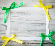 Paper frame with yellow and green bows. On a wooden background Stock Image