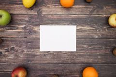 Paper and fruits on the edges of table.  royalty free stock photo