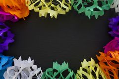 Paper garland background. Colored paper garland over a black background Stock Photos