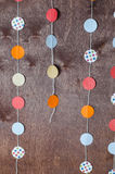 Paper garland. Paper holiday garland on a brown background Stock Photography