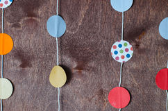 Paper garland. Paper holiday garland on a brown background Stock Image