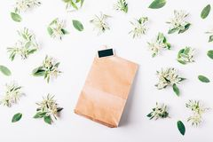 Paper gift bag and green flowers. On a white table top view Royalty Free Stock Image