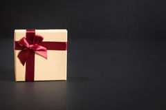 Paper gift box with deep red ribbon and a bow, on black Stock Images
