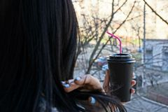 A paper glass with coffee in the hand of a girl with black hair. Big paper glass with coffee in the hand of a girl with black hair Royalty Free Stock Images