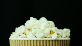A paper glass of popcorn, slowly and smoothly rotates on a black background.  Royalty Free Stock Photography