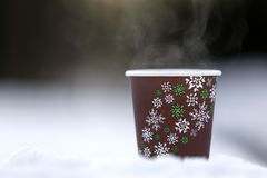 Paper glass on snow with hot drink. Brown paper glass with snowflakes with hot drink on snow royalty free stock photo
